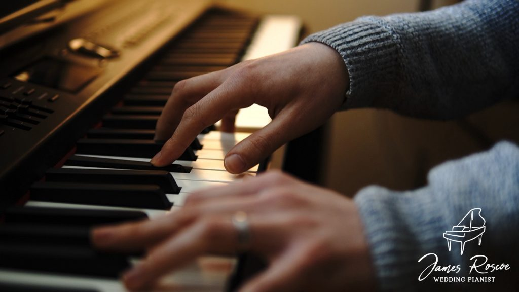 Close-up of James Roscoe playing piano with hands on keyboard