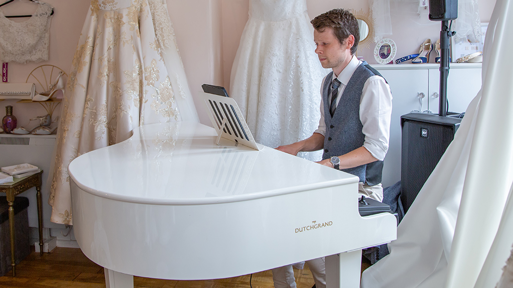 James Roscoe playing his portable white baby grand piano at Maisie Darling.